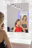 Belle fille deux élégante sexy dans des robes de soirée rouges et noires avec la coiffure lumineuse de soirée de maquillage de so Photos stock