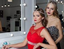 Belle fille deux élégante sexy dans des robes de soirée rouges et noires avec la coiffure lumineuse de soirée de maquillage de so Photo libre de droits