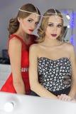 Belle fille deux élégante sexy dans des robes de soirée rouges et noires avec la coiffure lumineuse de soirée de maquillage de so Image libre de droits