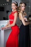 Belle fille deux élégante sexy dans des robes de soirée rouges et noires avec la coiffure lumineuse de soirée de maquillage de so Photo stock