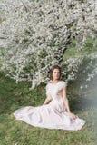 Belle fille douce tendre dans une robe rose avec un arbre de floraison proche de coiffure une journée de printemps ensoleillée photographie stock libre de droits