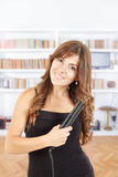 Belle fille employant le styler sur ses cheveux brillants Photos libres de droits