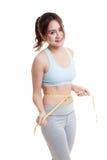 Belle fille en bonne santé asiatique mesurant sa taille Photographie stock libre de droits