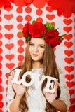 Belle fille en guirlande rouge des fleurs avec l'amour de mot Photo stock