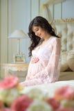 Belle fille enceinte dans un déshabillé de dentelle se reposant sur un lit des roses Photos stock