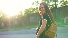 Belle fille enceinte, dans un T-shirt et avec un sac à dos, dans les rayons du coucher de soleil, frottant son ventre et banque de vidéos