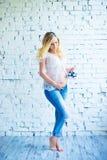 Belle fille enceinte rousse avec des espadrilles de bébé Image stock
