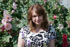 Belle fille entourée par la mauve colorée de fleurs Photographie stock libre de droits