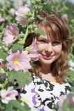Belle fille entourée par la mauve colorée de fleurs Image stock