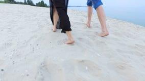 Belle fille et son ami marchant le long du bord de la mer - les pieds sont dans le sable banque de vidéos