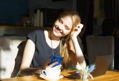 Belle fille européenne mignonne à la table dans un café, avec une tasse d'ordinateur portable et de téléphone de café, souriant r images stock
