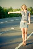 Belle fille faisant de l'auto-stop sur la route Images stock