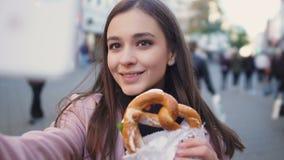 Belle fille faisant la vidéo au sujet du bretzel allemand traditionnel, blog culinaire clips vidéos