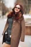 Belle fille fascinante sexy de brune dans une robe et un manteau de fourrure verts élégants avec une fourrure pelucheuse, des gan Image stock
