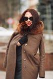 Belle fille fascinante sexy de brune dans une robe et un manteau de fourrure verts élégants avec une fourrure pelucheuse, des gan Photographie stock