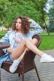 Belle fille gaie mignonne dans une robe lumineuse avec les cheveux bouclés et le maquillage lumineux se reposant à un café extéri Photo libre de droits
