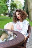 Belle fille gaie mignonne dans une robe lumineuse avec les cheveux bouclés et le maquillage lumineux se reposant à un café extéri Photographie stock libre de droits