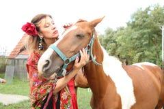 Belle fille gitane dans des vêtements lumineux avec un cheval à une ferme image stock
