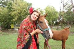 Belle fille gitane dans des vêtements lumineux avec un cheval et son poulain à une ferme photos stock