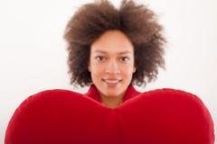 Belle fille heureuse avec l'oreiller rouge en forme de coeur Photos libres de droits