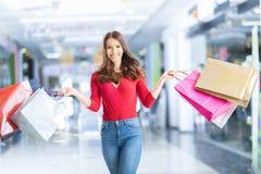 Belle fille heureuse avec la carte de crédit et paniers dans le shopp image stock