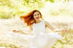 Belle fille heureuse de gingembre dans une robe blanche de cru de vol dans t images libres de droits