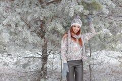 Belle fille heureuse gaie avec les cheveux rouges dans un chapeau et une écharpe chauds jouant et dupant autour dans la neige dan Images stock