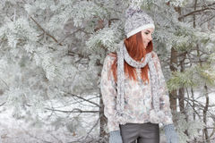 Belle fille heureuse gaie avec les cheveux rouges dans un chapeau et une écharpe chauds jouant et dupant autour dans la neige dan Images libres de droits