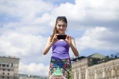 Belle fille heureuse photographiée à un téléphone portable Photos stock