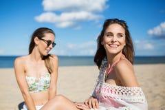 Belle fille heureuse s'asseyant sur la plage avec l'ami regardant loin Photo stock