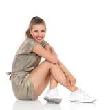 Belle fille heureuse s'asseyant sur un plancher Photos libres de droits