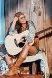 Belle fille hippie en bandeau et verres se reposant avec une guitare photo stock