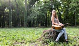 Belle fille hippie jouant la guitare Photographie stock