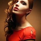 Belle fille inaccessible de gingembre dans la robe orange Photographie stock libre de droits