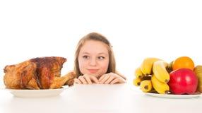 Belle fille jetant un coup d'oeil au-dessus du poulet cuit image stock
