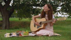 Belle fille jouant la guitare acoustique en parc banque de vidéos