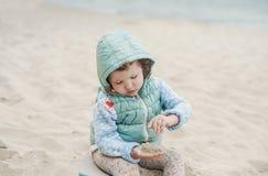 Belle fille jouant sur la plage dans le gilet chaud Photos stock