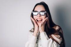 Belle fille joyeuse étonnée de femme en verres 3d sur le fond blanc réalité virtuelle, cinéma, technologie moderne Image libre de droits