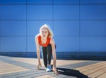 Belle fille - la blonde est sur un bas début, devant la course Jour extérieur Image libre de droits