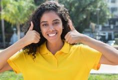 Belle fille latino-américaine avec de longs cheveux foncés montrant les deux pouces Image libre de droits