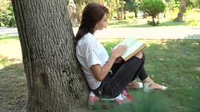 Belle fille lisant un livre en nature, apprenant le concept banque de vidéos