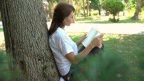 Belle fille lisant un livre en nature, apprenant le concept clips vidéos