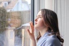 Belle fille mélancolique d'adolescent dans le châle bleu-clair semblant extérieur par des gouttes de pluie sur la fenêtre humide photo libre de droits