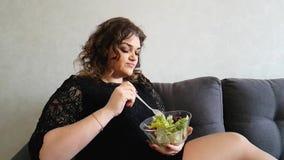 Belle fille mangeant de la salade l'apéritif affamé d'émotion de dégoût de stupéfaction de divan banque de vidéos