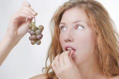 Belle fille mangeant des raisins image stock