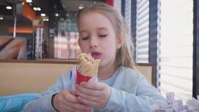 Belle fille mangeant un hot dog dans un caf? de bord de la route Aliments de pr?paration rapide dans le concept automatique de vo banque de vidéos