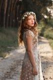Belle fille marchant dans la forêt sur le coucher du soleil Image stock