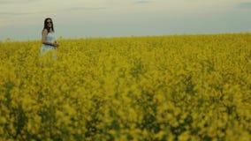Belle fille marchant dans le domaine des fleurs jaunes Sourires et rires banque de vidéos