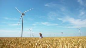 Belle fille marchant sur le champ du blé jaune avec des moulins à vent pour la production de courant électrique banque de vidéos