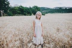 Belle fille mignonne dans un domaine de blé Photos stock